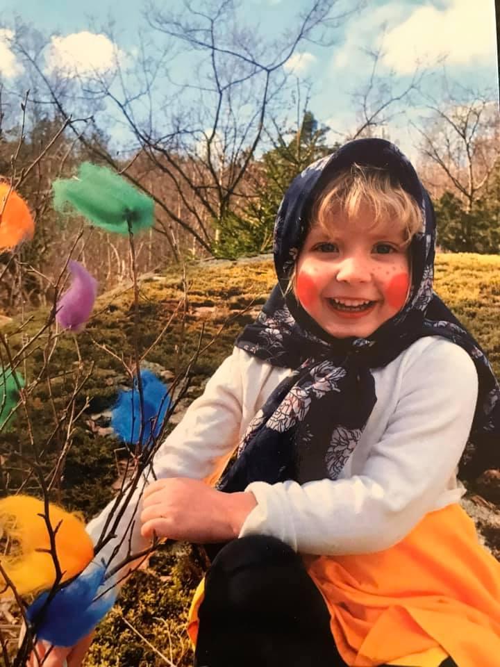 Glad Påsk önskar finaste påskkärringen Molly. en flicka utklädd till påskkärring och håller ett fägglatt påskris i handen