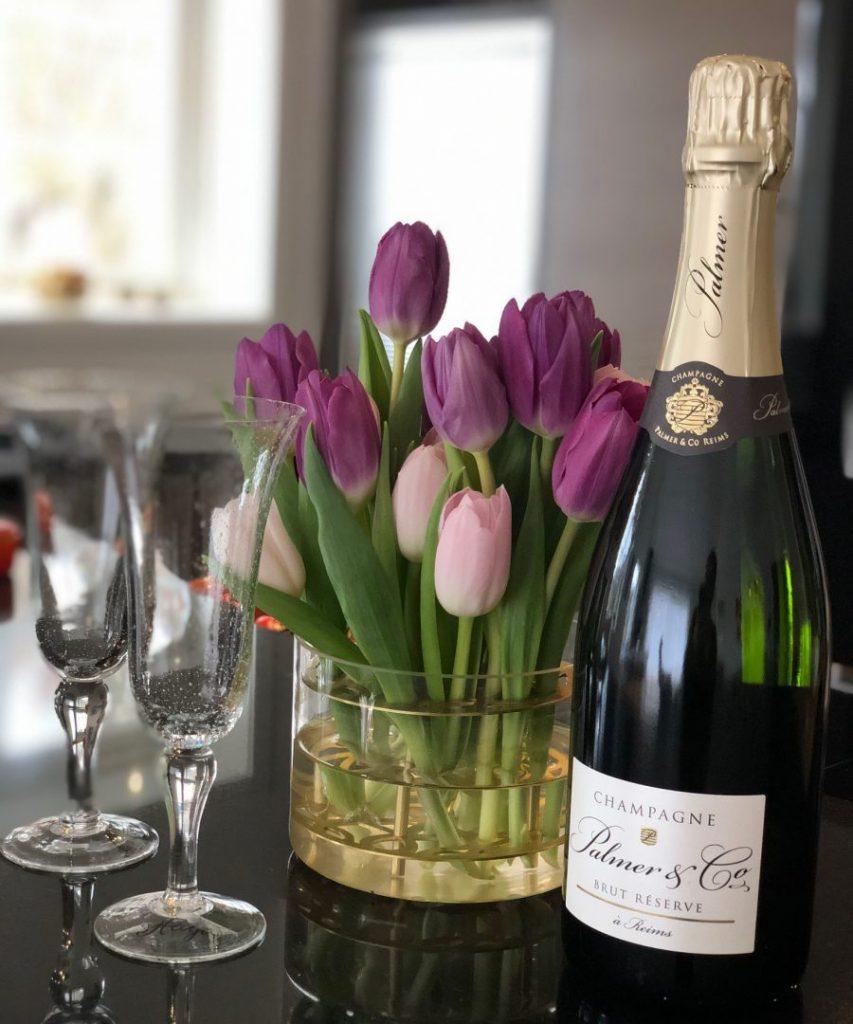 Champagneflaska glas och blommor på releaseparty